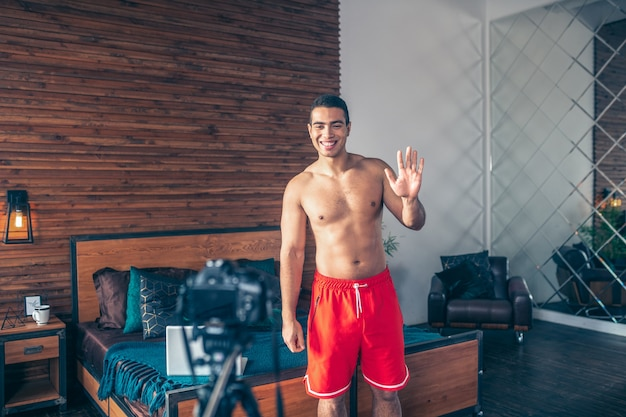 彼の信者に挨拶する赤いショートパンツで若いフィットスポーツvlogger