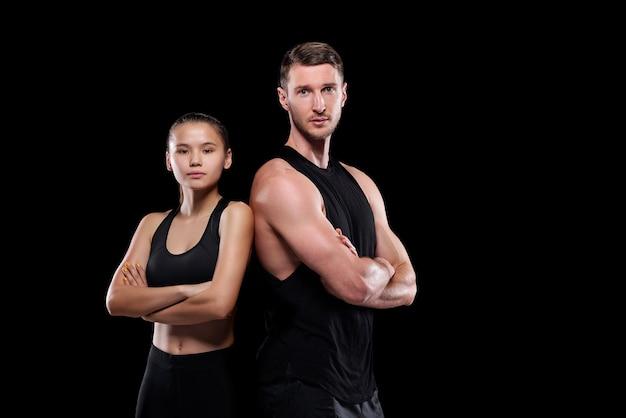 Молодой подтянутый спортсмен и спортсменка в черной спортивной одежде стоят рядом, скрестив руки на груди