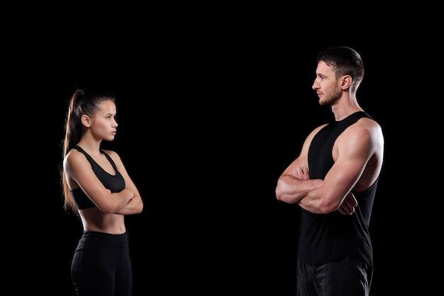 Молодой подтянутый спортсмен и спортсменка со скрещенными руками, стоящими друг напротив друга