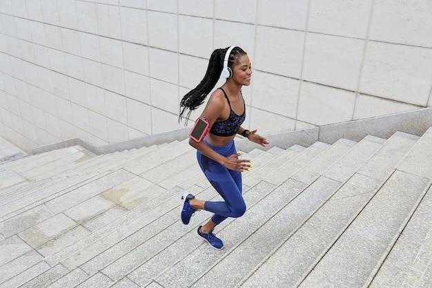 Молодая спортивная спортсменка наслаждается хорошей музыкой в наушниках во время пробежки по городу