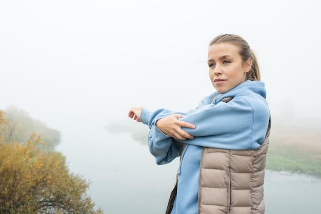 自然環境で運動しながら自分の前で左腕を伸ばす青いパーカーと灰色のジャケットの若いフィットスポーツウーマン