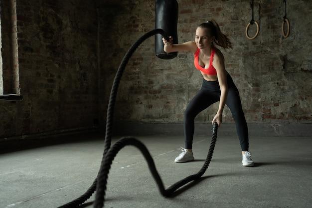 Молодая здоровая спортсменка, тренирующаяся в тренажерном зале для фитнеса, женщина, тренирующаяся с боевыми веревками в тренажерном зале