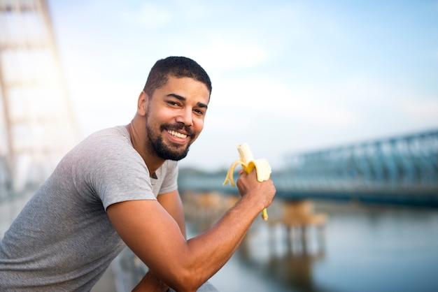 젊은 맞는 바나나를 먹고 웃는 스포티 한 사람