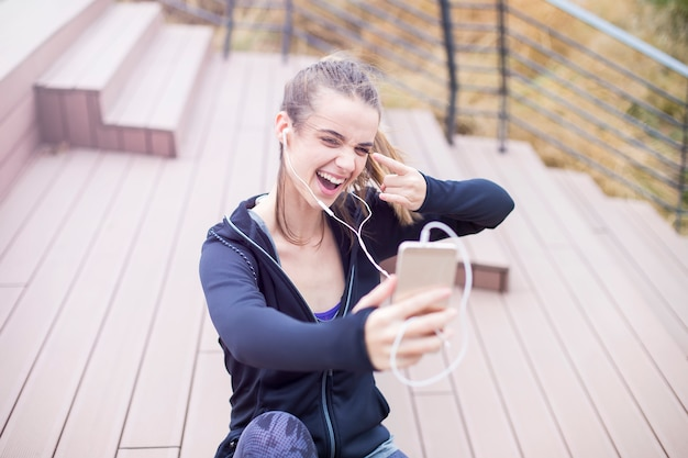 Young  fit sporty woman resting and listen music on mobile phone after  training