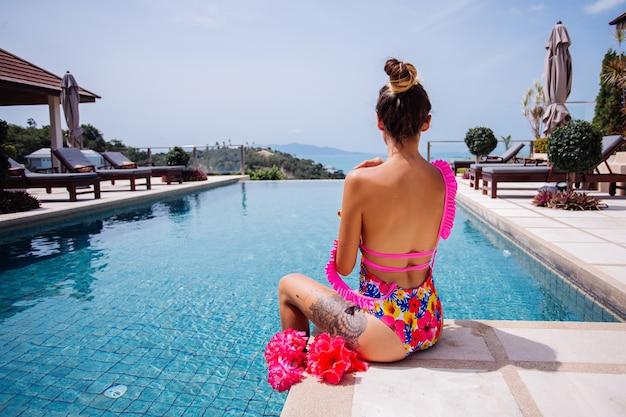 Молодая подтянутая загорелая татуированная женщина в довольно модном купальнике с розовыми цветами с открытой спиной на краю пейзажного бассейна