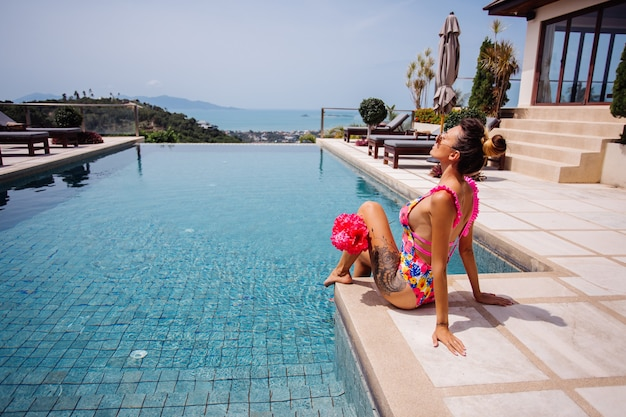 Young fit tanned tattooed woman in pretty trendy pink flower swimsuit open back on edge of infinity swimming pool