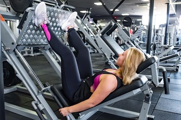 다리 프레스 기계와 다리 근육 운동을 하 고 체육관에서 젊은 맞는 여자. 가중 다리 훈련 기계로 운동하는 피트니스 룸에서 여성 운동 선수