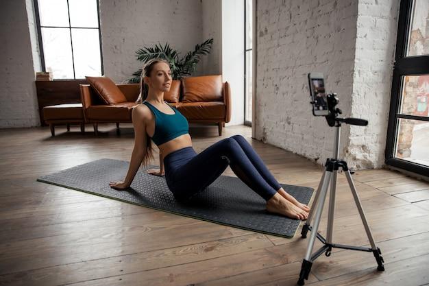 Молодая подтянутая женщина-блогер в спортивной одежде снимает видео на телефон, делая упражнения дома в гостиной. фото высокого качества