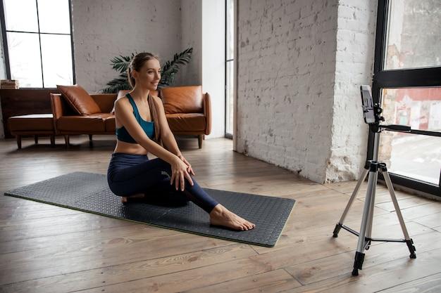 Молодая подтянутая женщина-блогер в спортивной одежде снимает видео на телефон, делая упражнения дома в гостиной.
