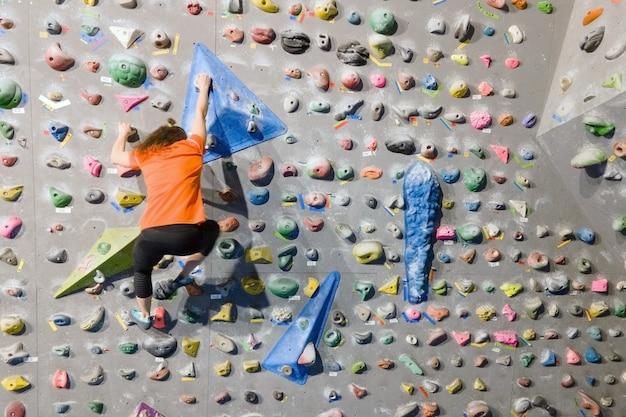 屋内の岩壁に登る若いフィットの女性。