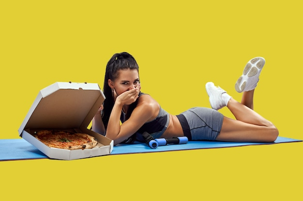 Young fit woman covers her mouth with her hand while lying on a fitness mat near a box with tasty fresh pizza. isolated.losing weight and getting fat concept