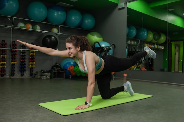 Young fit woman doing asana exercises in training class. endurance exercise, warm-up.