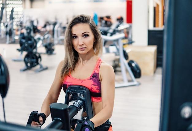 Молодая здоровая женщина делает упражнения для спины в тренажерном зале