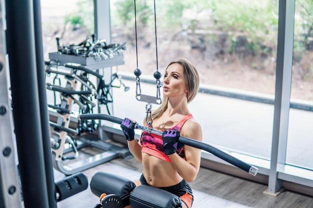 Молодая женщина пригонки делает упражнение тренировки бицепса в тренажерном зале.