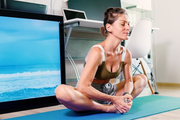 Young fit woman doing butterfly pose and stretching exercise indoor near tv screen on isolation at her home
