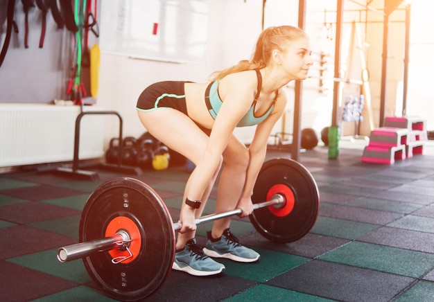 Young fit woman doing deadlift with a barbell in the gym. free weight training