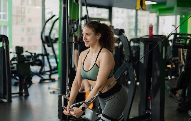 Молодая женщина подходит, упражнения на тренажере кроссовера. концепция здорового образа жизни. бодибилдинг и фитнес