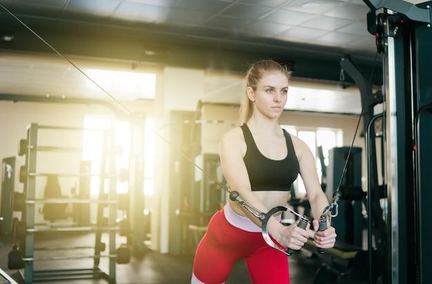 ジムでクロスオーバーマシンで運動をしている若いフィット女性