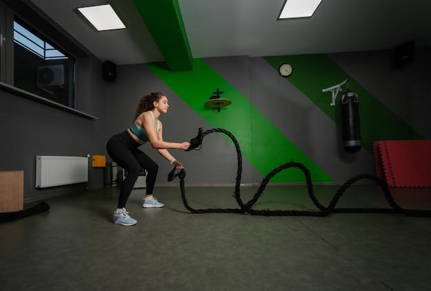 Молодая женщина подходит, упражнения с боевыми веревками в учебном классе. функциональная тренировка, тренировочный процесс.