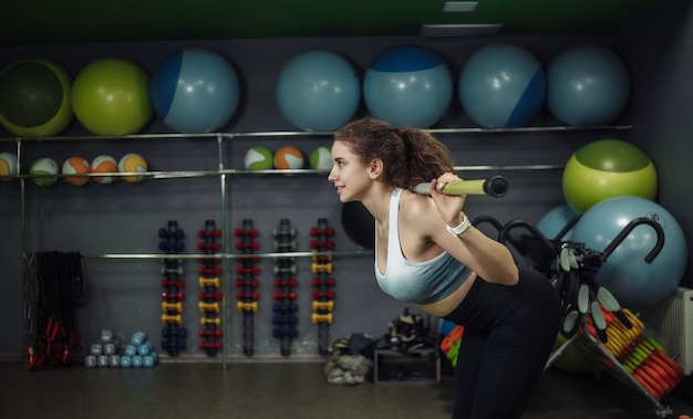 トレーニングクラスでフィットネススティックで運動をしている若いフィットの女性。
