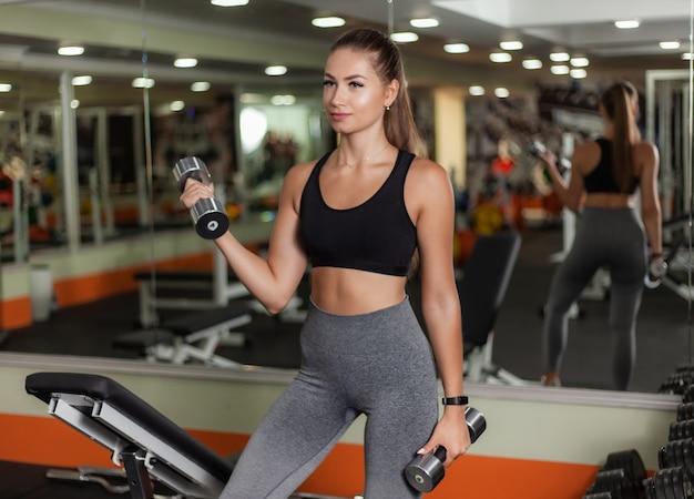 ジムでダンベルで上腕二頭筋のリフトを行う若いフィット女性。健康的なライフスタイルのコンセプト