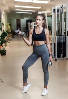 ジムにダンベルで上腕二頭筋のリフトを行うフィットの若い女性。健康的なライフスタイルのコンセプト