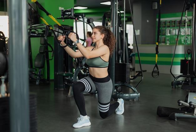 ジムでフィットネスストラップを使って突進運動をしている若いフィットの女性。ファンクショナルトレーニング。健康的な生活様式。フィットネスとボディービル