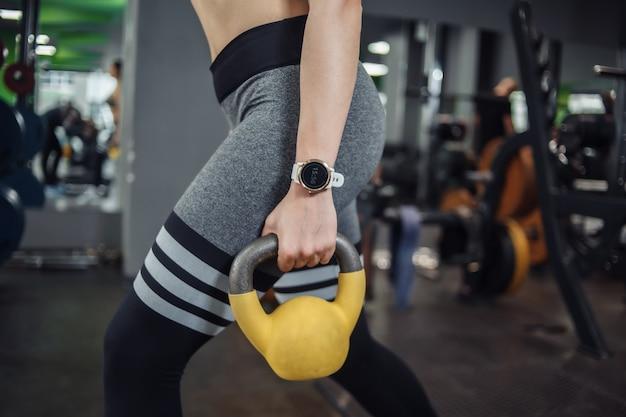ジムでケトルベルを使って突進運動をしている若いフィットの女性。フリーウェイト、ファンクショナルトレーニング
