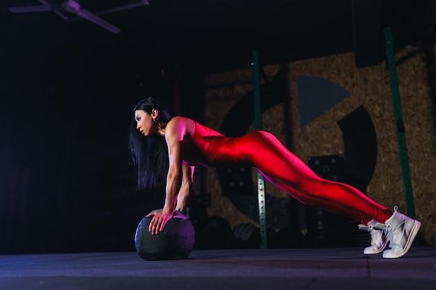 ジムで薬のボールのプッシュアップまたは板運動を行う若いフィット女性