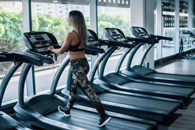 Молодая подходящая женщина делает упражнения в тренажерном зале на беговой дорожке беговой дорожки.