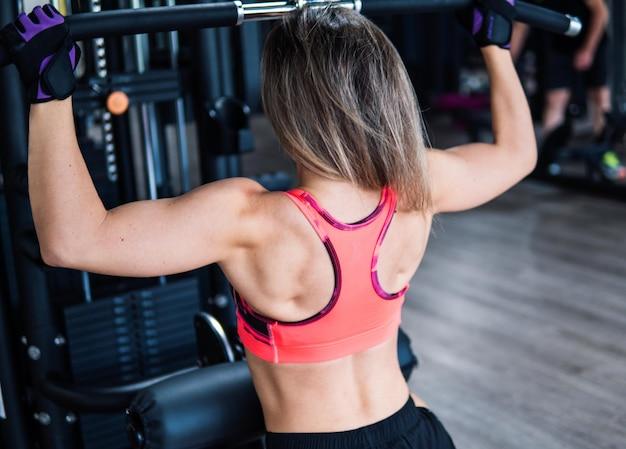 Молодая женщина подходит, упражнения плеч, используя тренажер в тренажерном зале. вид со спины.