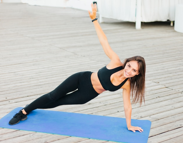 Young fit woman doing side plank on mat.