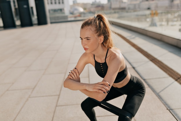 Young fit woman doing squats with a sports elastic band on the playground. high quality photo