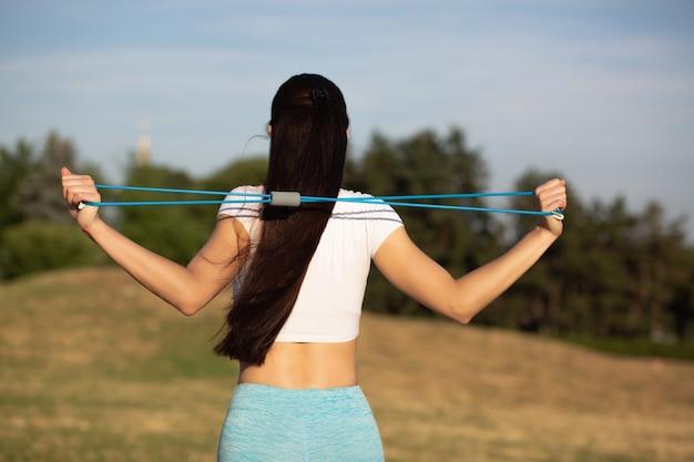 レジスタンスバンドでストレッチトレーニングをしている若いフィット女性