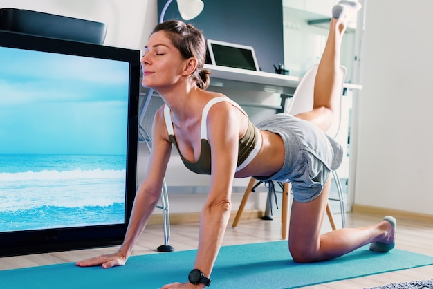 Young fit woman doing yoga dog or cat pose stretching exercise indoor near tv screen on isolation at her home
