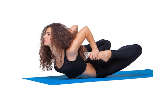 Young fit woman doing yoga exercises.