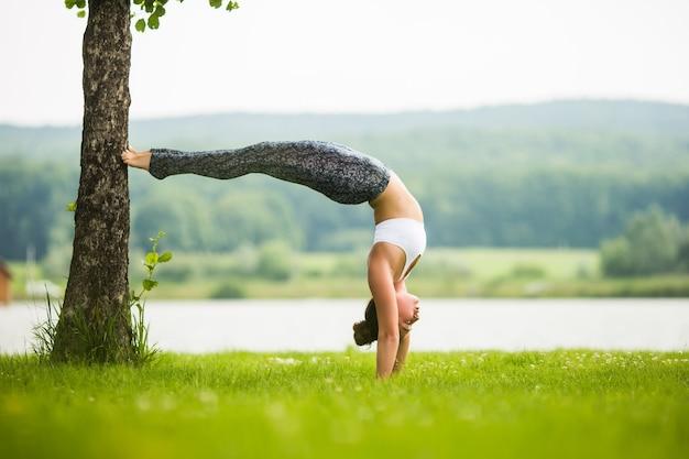 Молодая здоровая женщина занимается йогой в парке возле озера и дерева