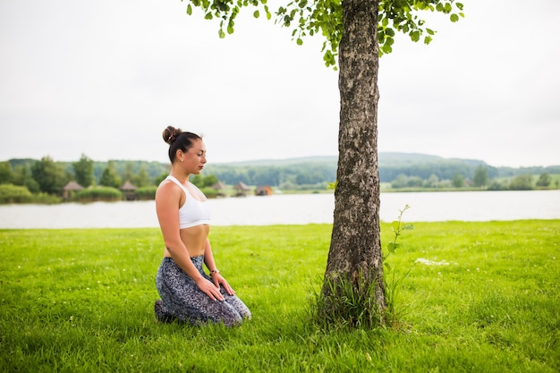 Young fit woman doing yoga in park near lake and tree