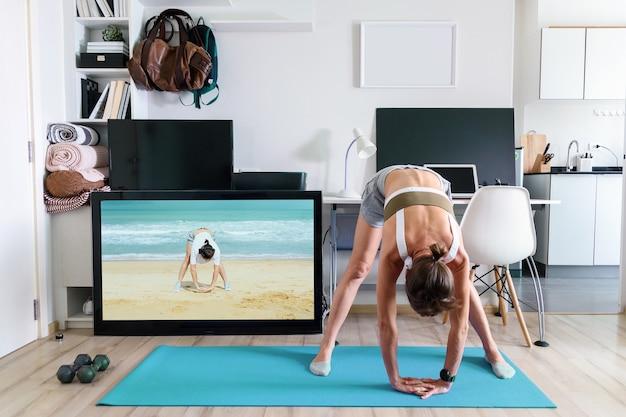 彼女の家で隔離のテレビ画面の近くで屋内でヨガのストレッチ運動をしている若いフィットの女性