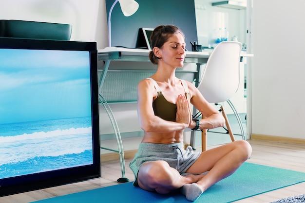 Молодая здоровая женщина делает упражнения на растяжку йоги в помещении возле экрана телевизора на изоляции в своем доме
