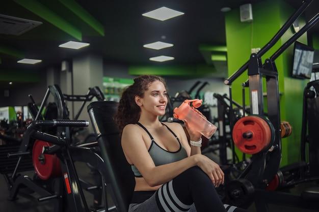 젊은 맞는 여자는 체육관에서 벤치에 앉아있는 동안 병에서 물을 마신다. 운동 사이에 휴식을 취하십시오. 건강한 라이프 스타일 컨셉