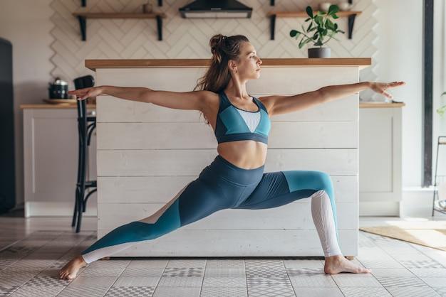 전사 포즈를 하 고 집에서 운동하는 젊은 맞는 여자.