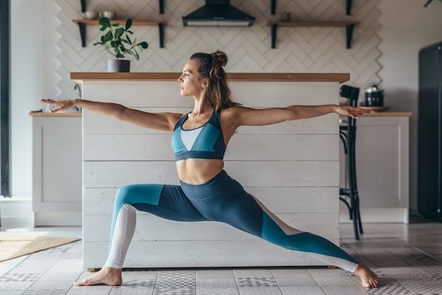 自宅でヨガの練習をしている若いフィットの女性。