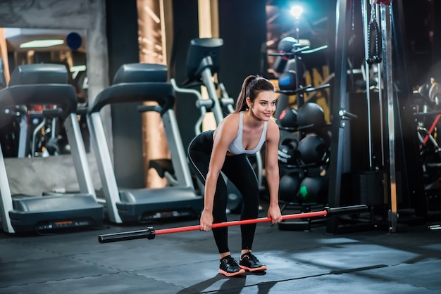 Young fit woman exercising with weighted workout bar in the gym.