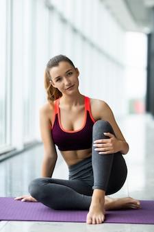 Молодая подтянутая женщина в спортивной одежде сидит на коврике во время физических упражнений над большим окном в развлекательном центре