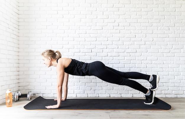 自宅で腕立て伏せをしている黒いスポーツウェアの若いフィット女性