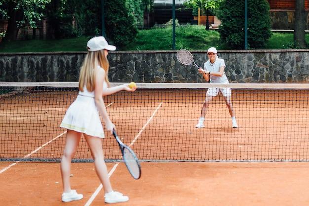 야외 테니스 코트에서 훈련하는 동안 모자와 테니스 유니폼을 입은 젊은 여성이 테니스 공을 제공합니다.
