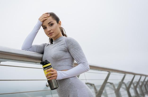 水のボトルを保持し、屋外に立っている灰色のスタイリッシュなスポーツウェアの若いフィットの女性。健康的なライフスタイルのコンセプト、アウトドアスポーツ
