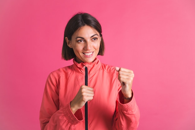 ピンクのスポーツウェアのジャケットを着た若いフィット感の女性は、ボックスのジェスチャーと戦う
