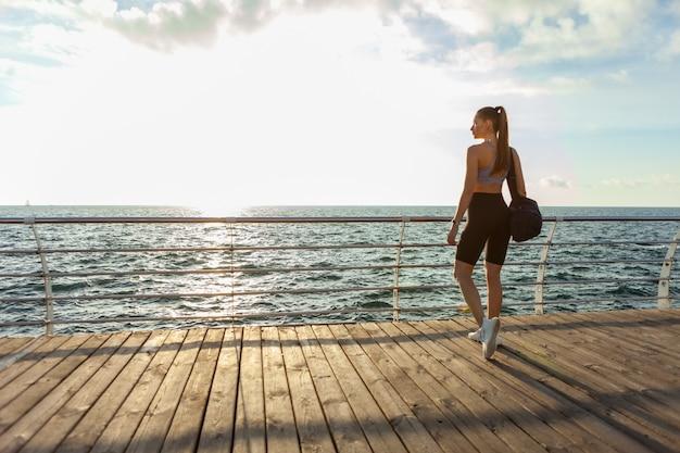 トレーニングバッグとスポーツ服を着た若いフィットの女性は、ビーチの日の出で朝のトレーニングに来ました